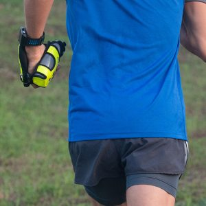 Man in blue shirt running with a green Fitletic HydraPalm bottle hand holder