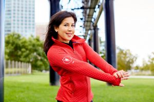 Michele Gordon Levy stretching her arms in a red zip up sweatshirt