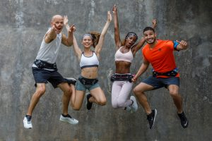 four people jumping wearing fitletic running belts
