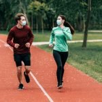 woman and man running with masks on running safety fitletic