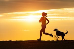 how to start running with your dog - woman and dog running at sunset