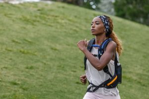 woman hiking through field in a fitletic hydration backpack